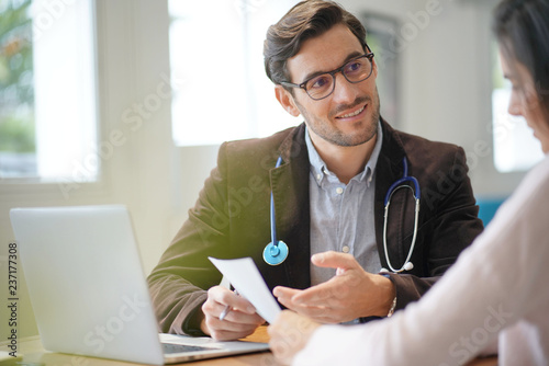 Fotografia  Modern young doctor speaking to patient in office