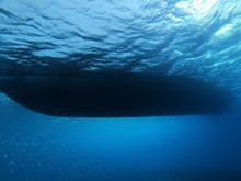 Big Ship From Down Underwater Top View With Shining Light Sky And Wavy Chop Water Like Clouds. Diving Picture With Deep Mood Athmosphere. Beauty Of Sea Oceans Dark Waters. Abstract Landscape Scenery