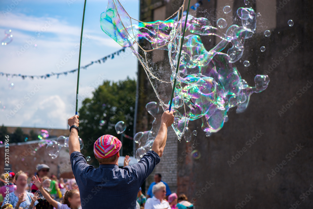 Fototapety, obrazy: A freelance clown blowing hundreds of tiny, small and big bubbles at outdoor festival in city center. Concept of entertainment, birthdays. Kids having fun. Shower of bubbles flying in the happy crowd