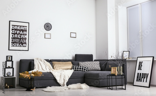 Stylish interior of room with comfortable sofa and golden decor