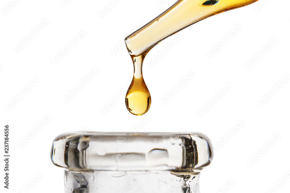 Fototapeta Dripping oil from pipette into glass bottle on white background