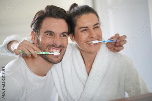 Staande foto Hoogte schaal Fun attractive couple brushing teeth together