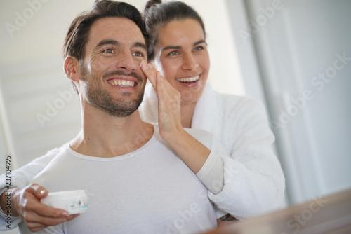 Fotografie, Obraz  Stunning brunette applying face cream on her handsome partner
