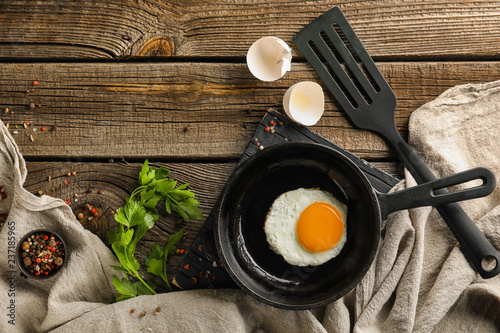 Fototapeta Pan with tasty fried egg on wooden table obraz