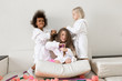 Little girls play with hair curlers and hairpins. Girls girlfriends in white coats braid curlers and hair clips each drg in her hair.