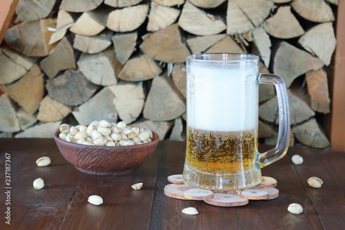 Tuinposter Bier / Cider Mug of light beer on the table against the background of firewood.