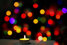 One Candle Burns On The Background Of Multi-colored Spots.