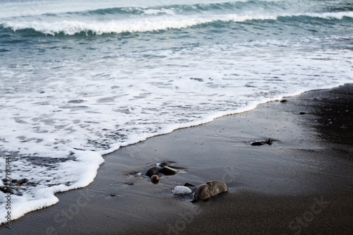 waves hitting the beach at black sand beach in reynisfjara on iceland