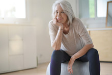 Smiling Elderly Woman Resting On A Swiss Ball At Home
