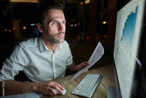 Fotografia  Focused man with document using computer