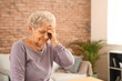 Senior woman suffering from headache at home