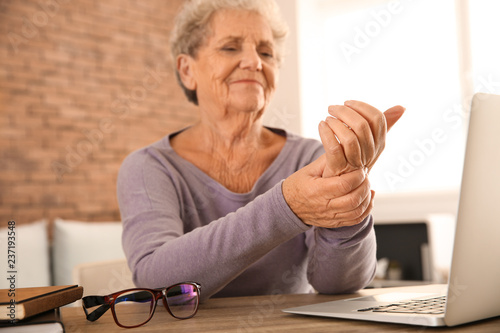 Senior woman suffering from pain in wrist while sitting at table with laptop Wallpaper Mural