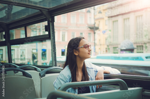 Fotografia  A girl in glasses with long dark hair sits inside a tour bus and looks into the camera and looks out the window
