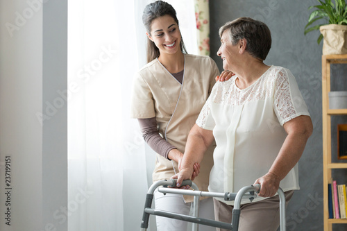 Photo  Smiling beautiful caregiver and disabled old lady with walker at home