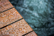 Selective Focus Of Droplet On Wooden Terrace With Koi Carp Japanese Pond In Raining Day.Top View.Pet,Home And Decor Concept.