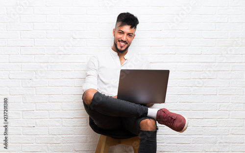 Fotografie, Obraz  Arabic young man with laptop sitting on a chair