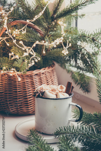 Winter warming mug of chocolate with marshmallow on windowsill with Christmas tree decor.