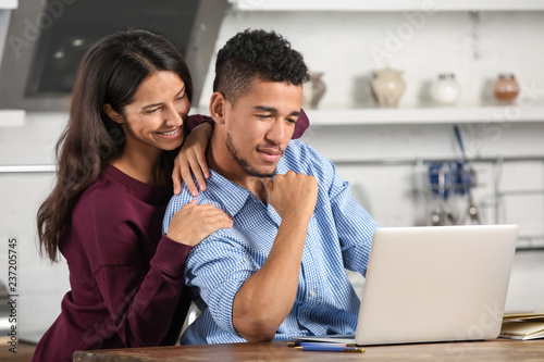 Fotografie, Obraz  Young couple with laptop in kitchen