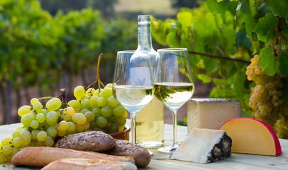 Wine, baguette, cheese against vineyard landscape
