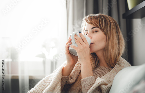 Happy woman in soft sweater relaxing at home with cup of hot tea or coffee Fototapeta