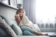 Happy Woman In Soft Sweater Relaxing At Home With Cup Of Hot Tea Or Coffee