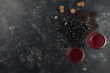 Red wine in glass goblets with grapes on a decorative board. On a dark background.