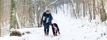 Woman With Her Dog Hiking Or Walking In Winter On A Snow Covered Path