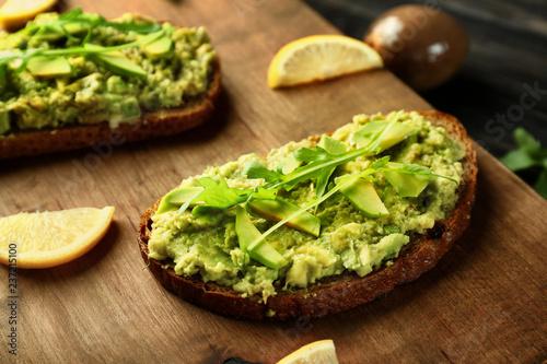 Pinturas sobre lienzo  Delicious avocado toasts on wooden board, closeup