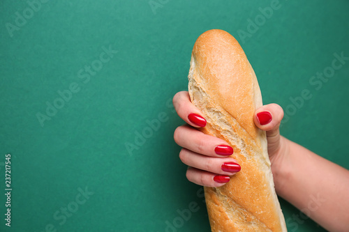 Woman holding fresh baguette on color background. Erotic concept