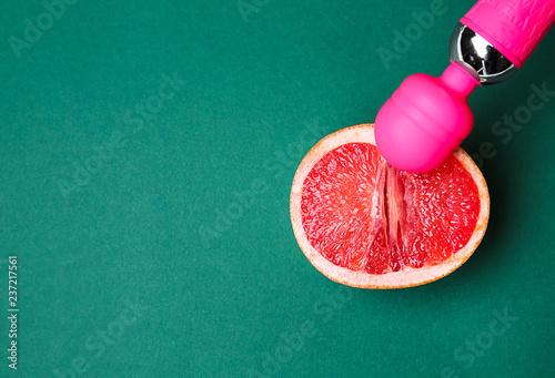 Fotografie, Obraz  Vibrator and half of grapefruit on color background