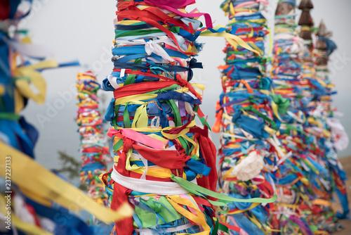 Deurstickers Paradijsvogel Colorful ribbons on wooden poles at Lake Baikal in Siberia