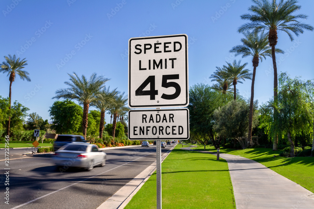 Fototapeta Speed Limit 45 Radar Enforced road sign with passing cars on a California street.