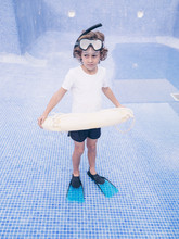 Boy In Diving Equipment With Lifebuoy In Empty Pool