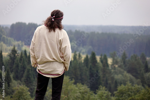 Fotografia  A young man in a traditional folk costume in nature, looking into the distance