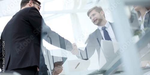 Fototapeta view through the glass.handshake of business partners .bottom view obraz