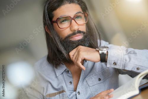 Fotografie, Tablou  Dark-haired man with eyeglasses reading book
