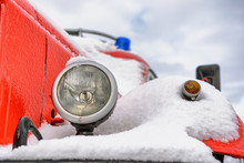 Headlamp Of An Old Red Fire Truck Covered With First Snow