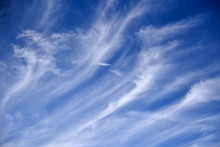 Long White Feathery Clouds On A Blue Sky