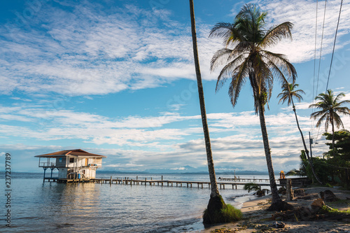 Small house with pier in tropical seascape