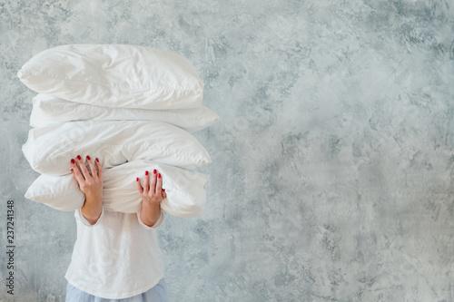 Obraz na plátně Woman holding big pile of white soft cozy pillows on gray background