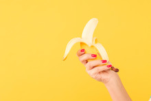 Woman Hand With Red Nail Polish Holding Peeled Banana On Yellow Background