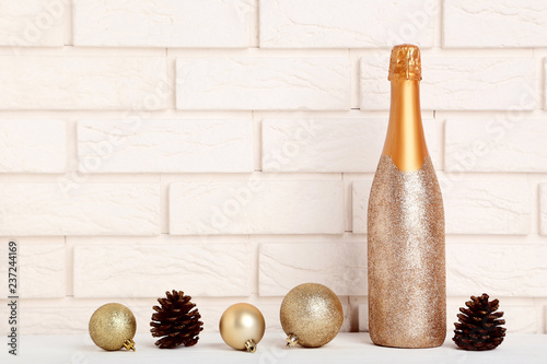Fotografía  Champagne bottle with christmas baubles and cones on brick wall background
