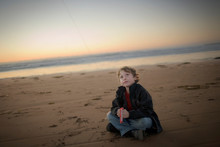 Young Boy Sitting On The Beach While Flying A Kite.