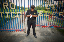 View Of A Security Guard Near A Gate.