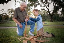 Grandfather Helping His Grandson To Build A Structure Out Of Wood In The Backyard.