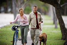 Mid-adult Woman Walking With A Bicycle As Her Husband Walk The Dog.