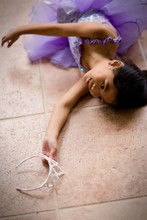 Young Girl Lying On The Floor Wearing A Tutu And Holding A Tiara.