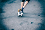 Fototapeta Sport - Legs, feet of football player, dribbling with the ball on asphalt in yard