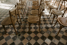 Wedding Ceremony Set Up With Wood Chairs And Flower Petals On Vintage 1900s Checkered Floor Tile