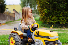 Blonde Little Girl Driving A Tractor In A Farm.